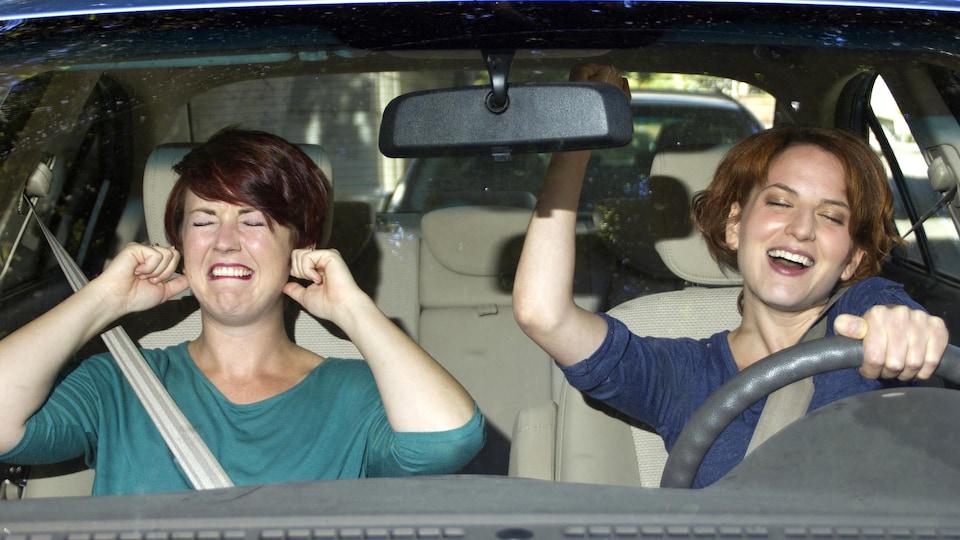 Une femme chante au volant pendant que sa passagère se bouche les oreilles.