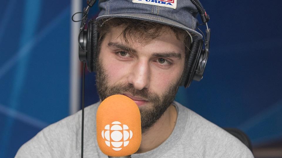 Le jeune homme porte une casquette et parle dans un micro.