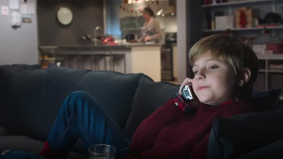 Un enfant assis sur un canapé discute au téléphone dans cette image tirée d'une publicité des Producteurs de lait du Québec.