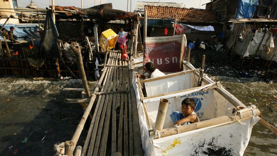 Un adulte et un enfant utilisent des latrines publiques se jetant dans la mer dans un bidonville de Jakarta, en Indonésie.