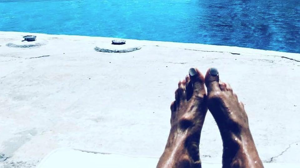 Les pieds d'Elle Macpherson au bord d'une piscine.