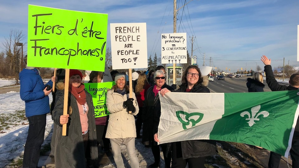 Des manifestants avec des enseignes et un drapeau franco-ontarien à Cambridge, en Ontario.