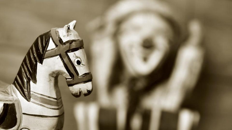 Photo sépia montrant la portion d'un cheval à bascule et d'autres jouets flous.