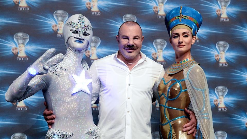 Thierry Mugler entouré de deux artistes costumés lors d'une première théâtrale en 2014.