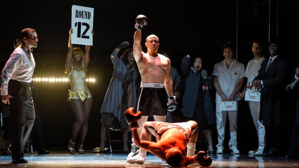 Un boxeur envoie au tapis son adversaire. Un arbitre se trouve à gauche, une femme tient une affiche indiquant « Round 12 » et des gens sont derrière le boxeur.