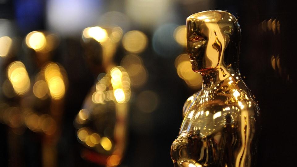 Des statuettes dorées de l'Académie des Oscars brillent sous l'éclairage.