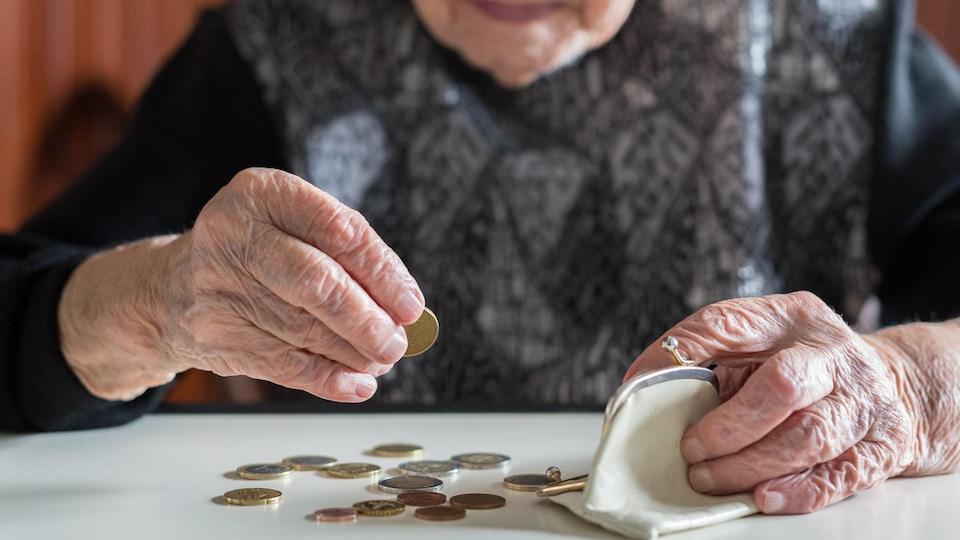 Une dame âgée compte ses sous, posés sur une table devant elle.