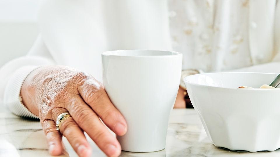 Une personne âgée devant un couvert à table.