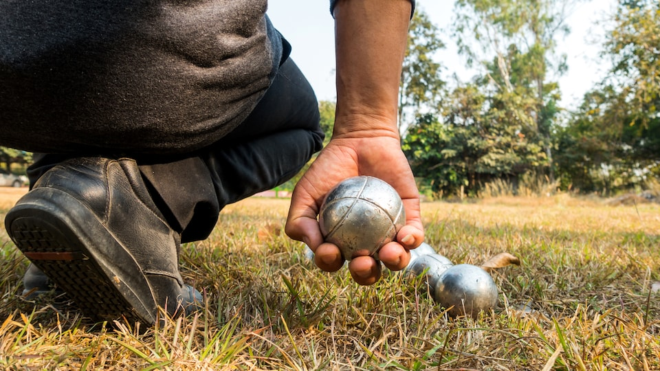 Un homme accroupi tient une boule de pétanque.