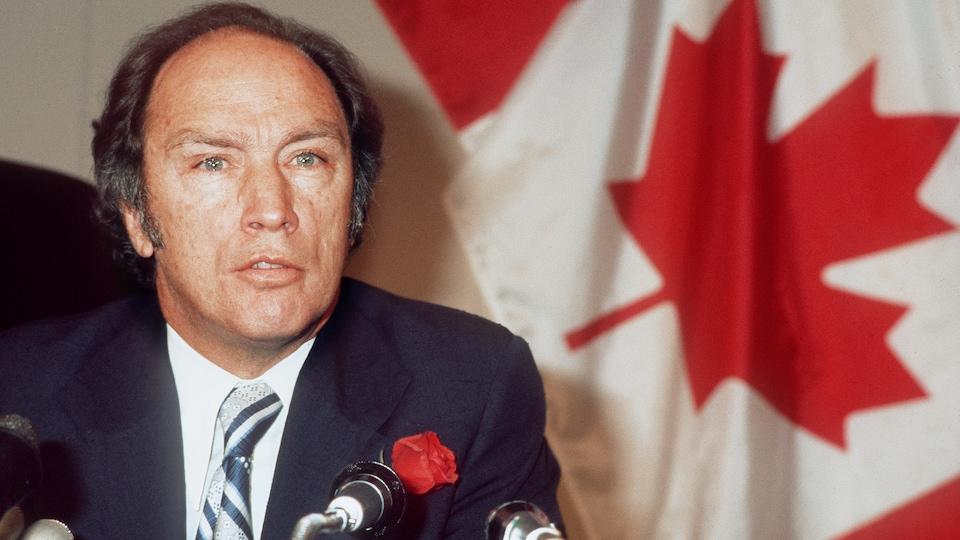 L'ancien premier ministre Pierre Elliott Trudeau devant un drapeau canadien en 1974.