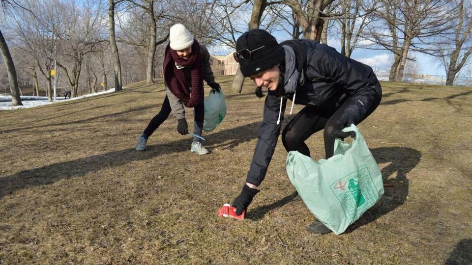 Des gens s'affairent à ramasser des déchets dans un parc.