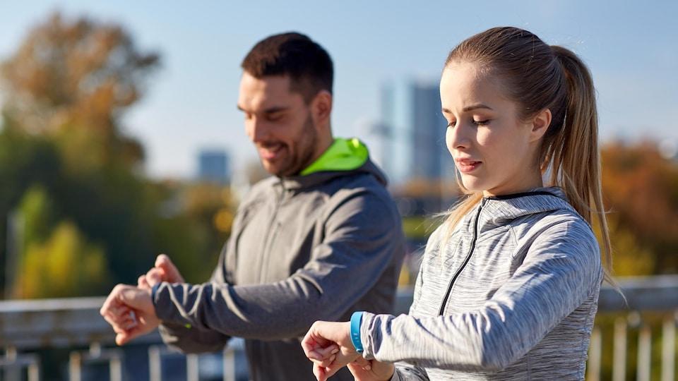 Deux sportifs à l'extérieur consultent leur bracelet connecté.
