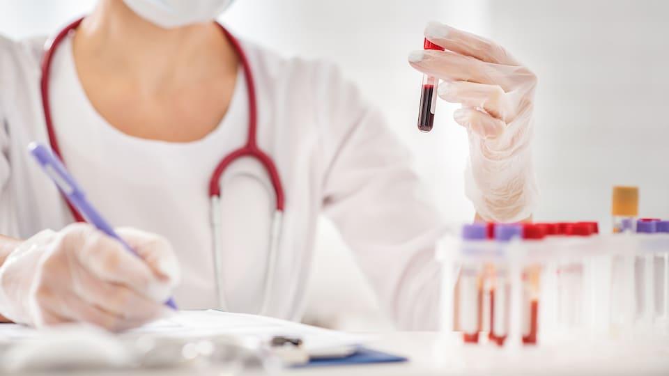 Une travailleuse médicale analyse un échantillon de sang contenu dans une éprouvette.