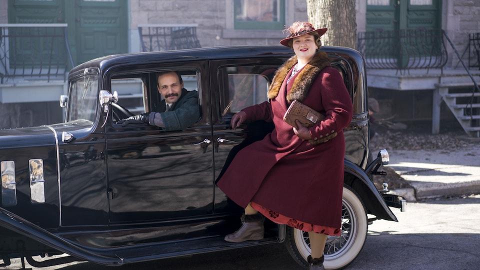 Émile Proulx-Cloutier est au volant d'une voiture d'époque stationnée et Debbie Lynch-White est debout à côté dans cette image tirée du film <i>La Bolduc</i>, de François Bouvier.