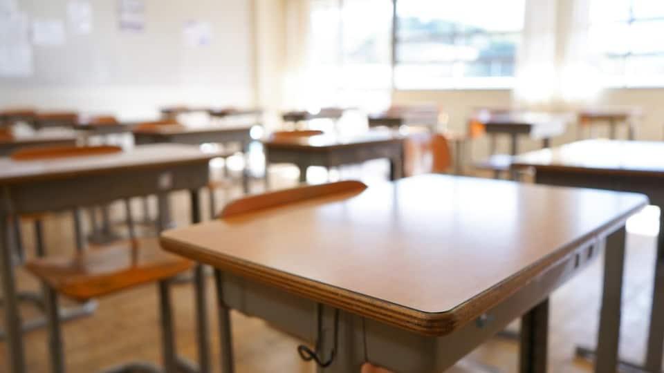 Des pupitres dans une classe d'école vide.
