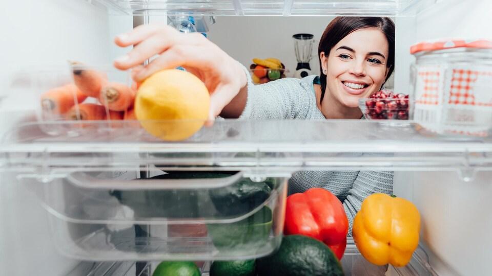 Une femme saisit un citron dans un réfrigérateur ouvert.