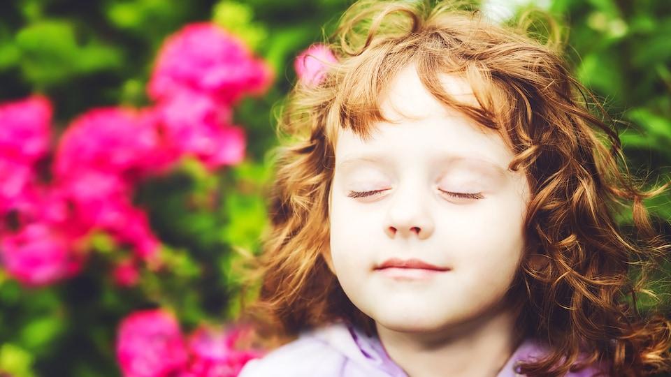 Une petite filles hume paisiblement l'air ambiant, les yeux fermés.