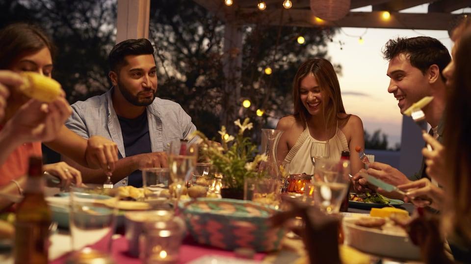 Des gens mangent, discutent et rient autour d'une table remplie de plats et de verres.