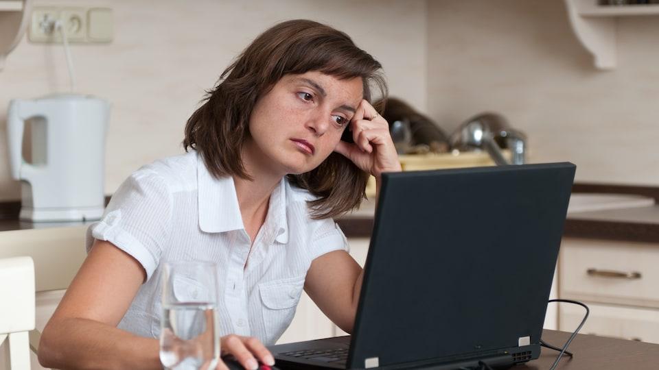 Une femme assise dans sa cuisine semble s'ennuyer devant son écran d'ordinateur.
