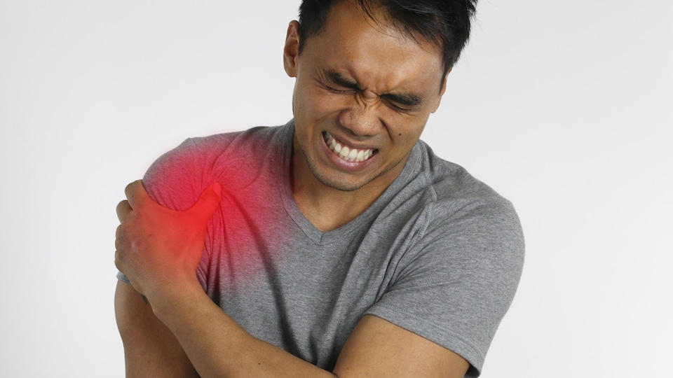 Un homme fait une moue de douleur en se tenant l'épaule.