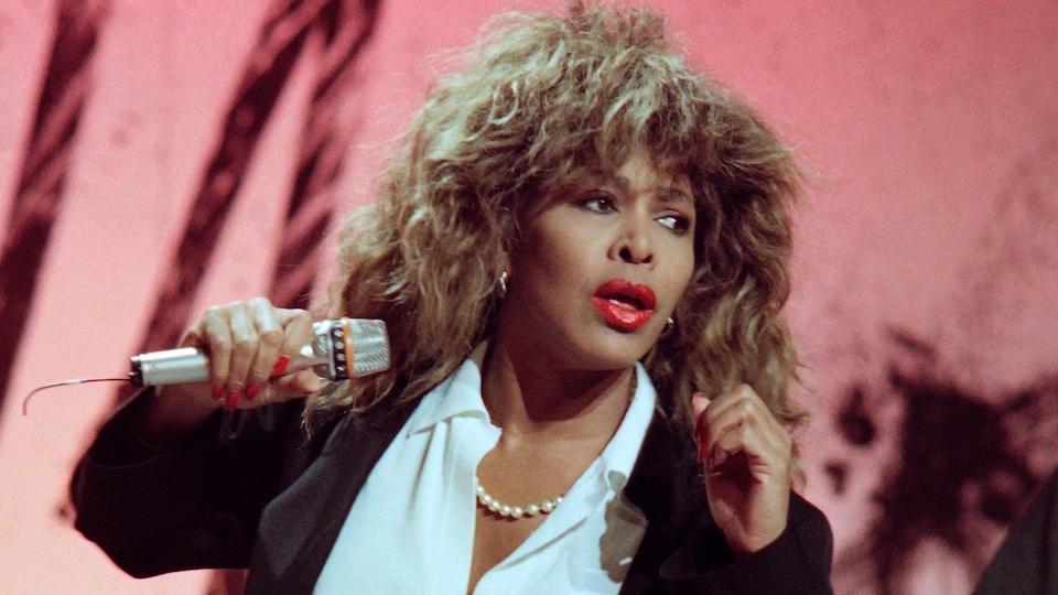 Tina Turner en mouvement sur scène, un microphone à la main.