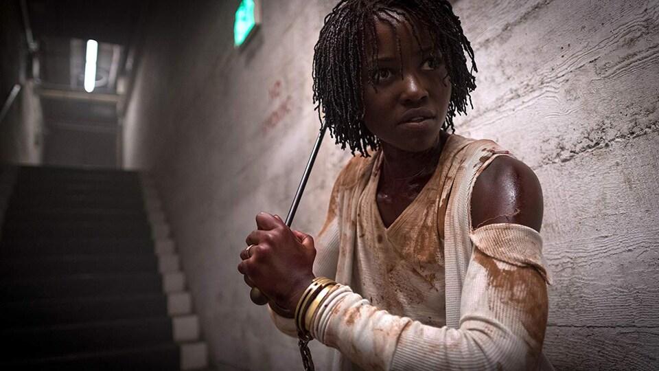 Lupita Nyong'o tient une tige de métal en guise d'arme sur cette image tirée du film <i>Us</i>, de Jordan Peele.