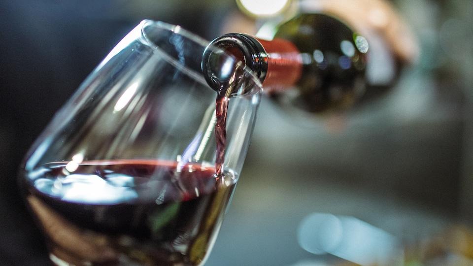 Du vin rouge est versé dans un verre.