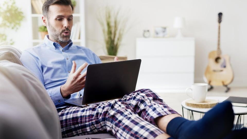 Un homme portant une chemise et un pantalon de pyjama tenant un ordinateur portable.