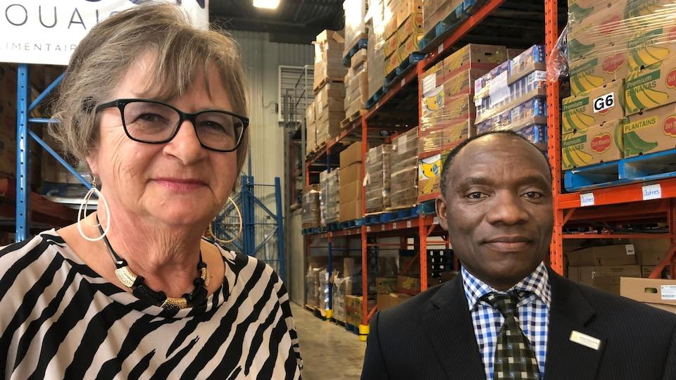 Diane Dupont-Cyr, présidente du C. A., et ArmandKayolo, directeur général de Moisson Outaouais dans l'entrepôt de l'organisme.