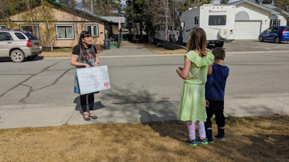 Une femme avec un tableau parle à deux enfants devant une maison