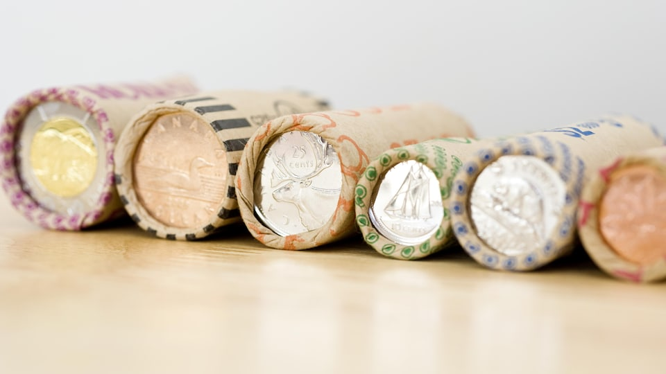 Des rouleaux de monnaie placés côte à côte, de la pièce d'un sou à a pièce de deux dollars.