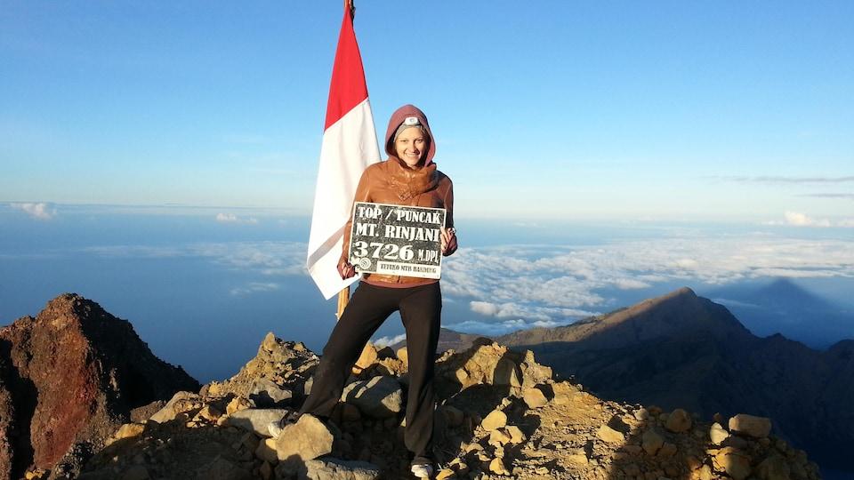 Au sommet du mont Rinjani, Priscilla Pilon tient une affiche qui indique 3726 mètres.