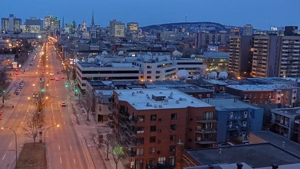 C'est le début de la soirée : quelques voitures circulent sur le boulevard René-Lévesque. Les lampadaires, les feux de circulation et l'éclairage des tours à bureaux brillent dans le paysage. Sur la gauche se trouve la grande tour de la Maison de Radio-Canada; vers le centre, la tour d'Hydro-Québec; et complètement vers la droite, l'édifice de TVA.