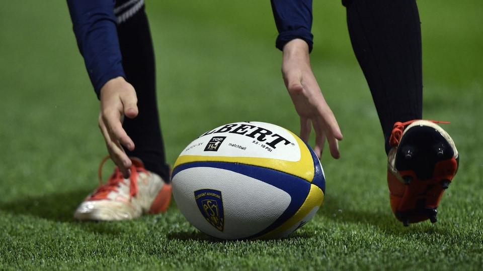 Un homme prend un ballon de rugby dans ses mains.