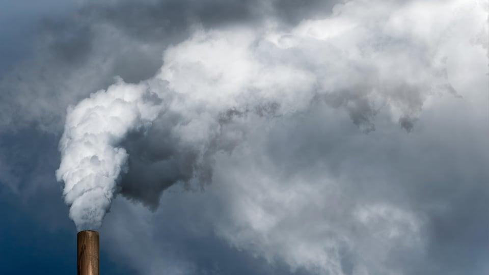 Une cheminée crache sa fumée dans le ciel.