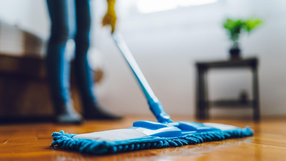 Une personne nettoie le plancher de son appartement.