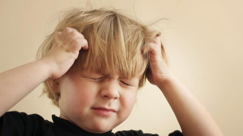 Un garçon se gratte en raison des poux.