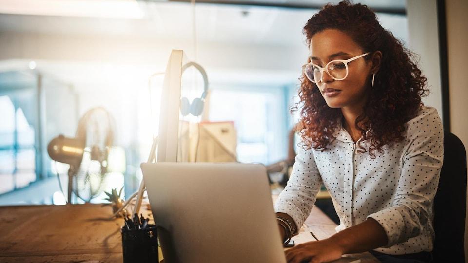 Une jeune femme d'affaires utilisant un ordinateur portable pendant une fin de soirée au travail.