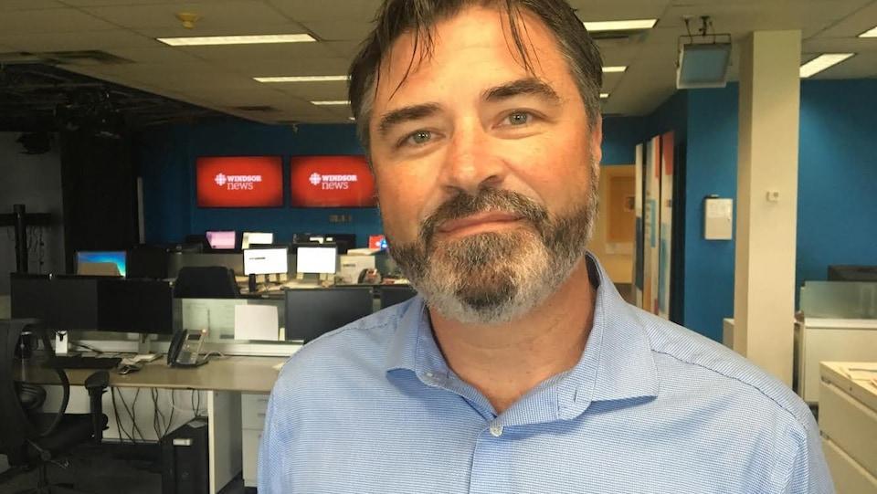 Portrait de Kieran McKenzie. Il porte une barbe et une chemise.