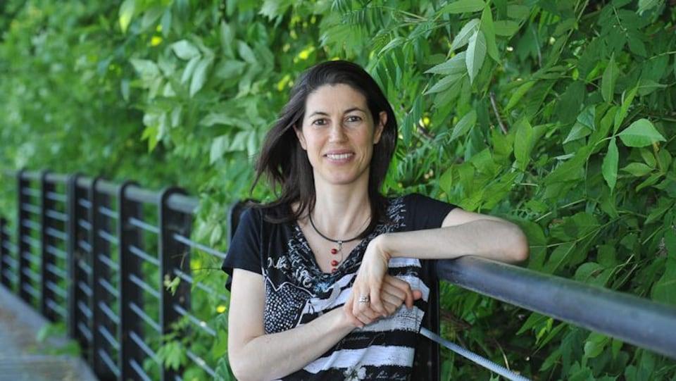 Luisa Veronis, professeure agrégée au département de géographie, environnement et géomatique à l'Université d'Ottawa, fait la pose, avec un bras accôté sur une rampe.