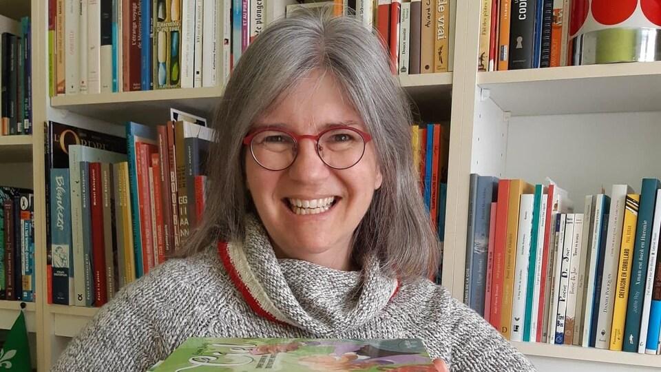 Mireille Messier tiens plusieurs livre devant sa bibliothèque