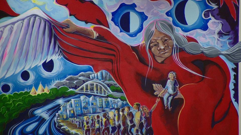 Une murale montre une aînée autochtone qui protège, de son châle transformé en aile, le peuple d'Edmonton qui retourne à la maison.
