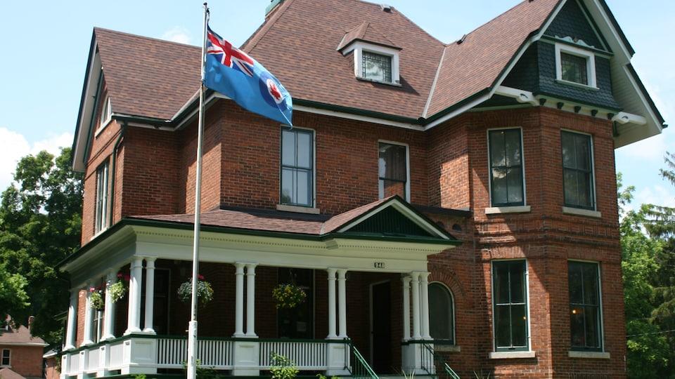 La maison vue de l'extérieur. Un drapeau de l'Aviation royale du Canada flotte devant.