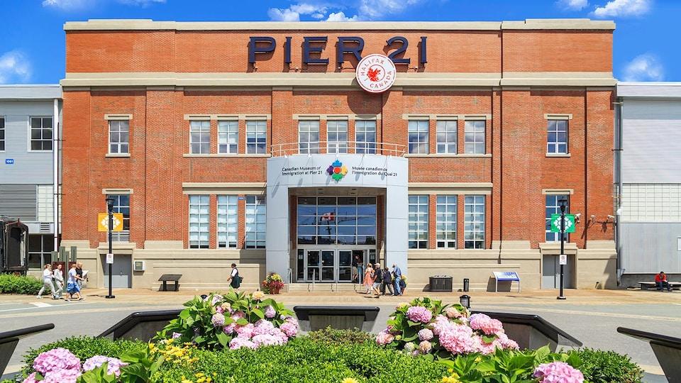 Devanture du Musée canadien de l'immigration du Quai 21, avec à l'avant, des fleurs.
