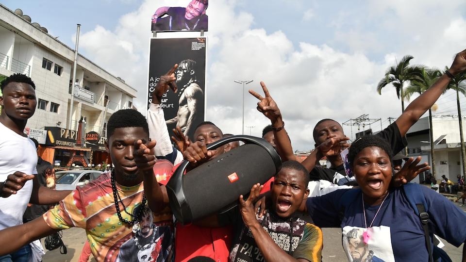Des Ivoiriens dans la rue dansent au son de la musique d'un appareil portatif.