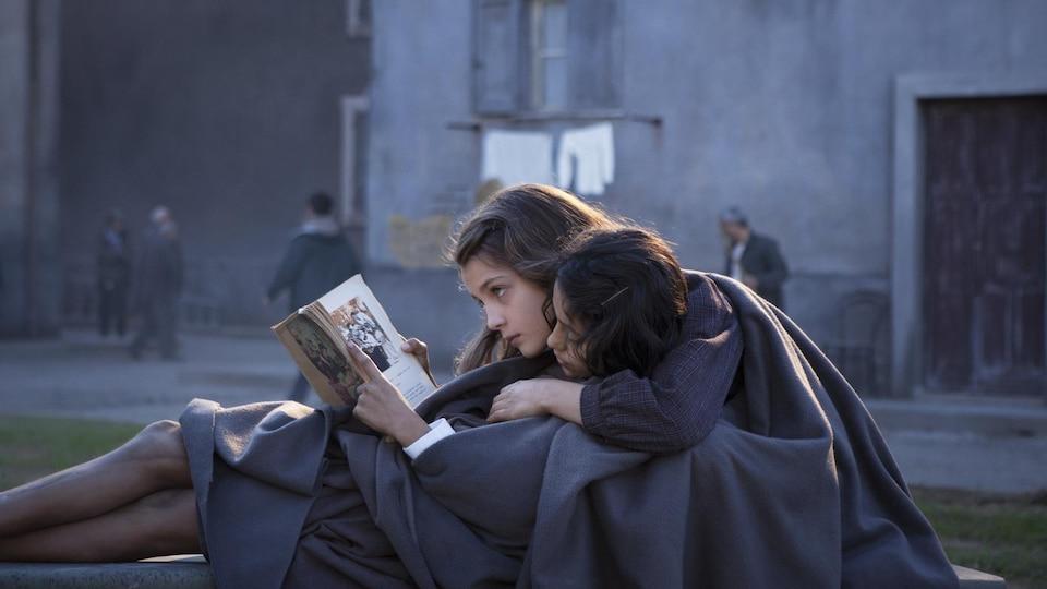 Deux fillettes lisent un livre.