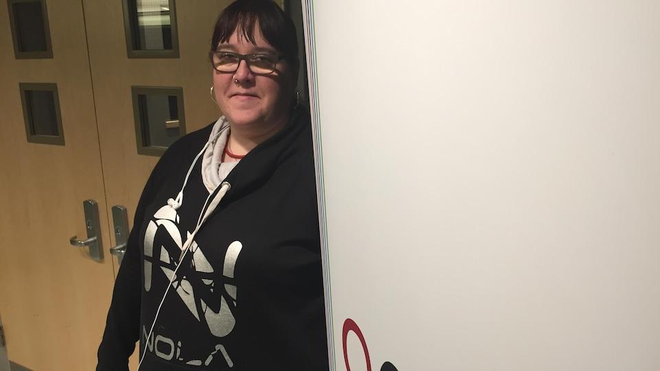 La directrice générale de l'APCM, Natalie Bernardin, près de la bannière de l'organisme.