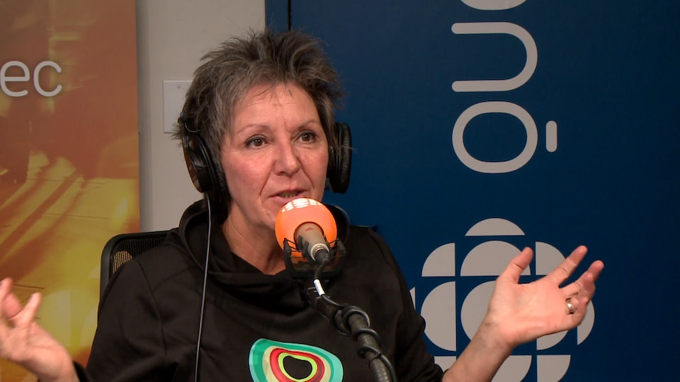 Une femme aux cheveux courts portant un pull sombre avec un motif fait de plusieurs cercles de couleurs parle au micro en agitant ses mains.