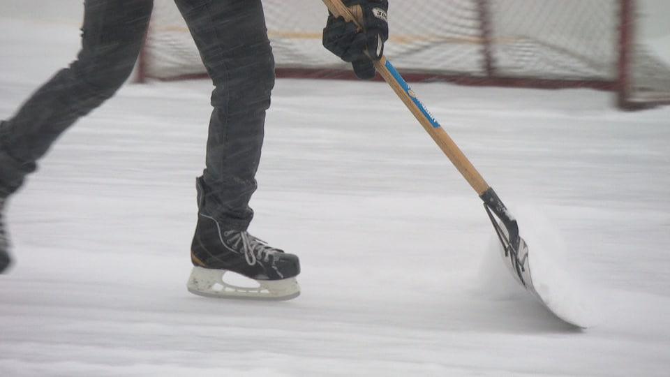 Un homme pousse une pelle pour déblayer sur une patinoire extérieure de hockey.