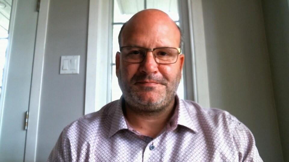 Nicolas Prévost, avec une chemise à carreaux et des lunettes